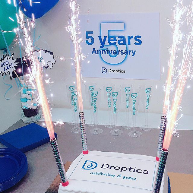 "A birthday cake with sparklers. The sign above reads ""The 5th anniversary of Droptica"""