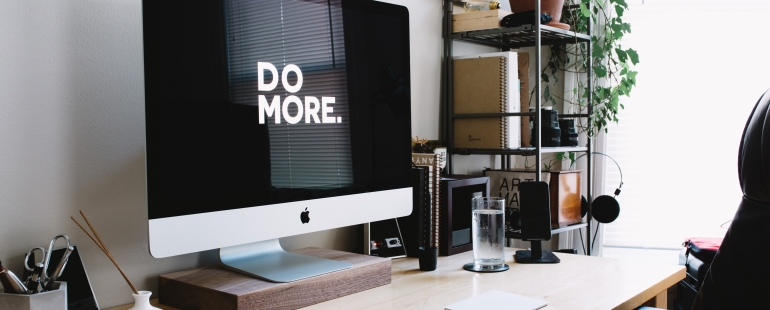 "A view of the room. Desk with the computer on the top is isible. On the screen there's a dark-themed website displayed with ""Do more"" slogan at the center"