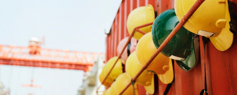 Yellow and green hardhats for several teams of builders hanging from a contenair