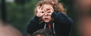 A girl making binocular gesture as in searching for something. Maybe she's looking for your drupal website in google?